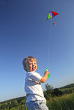 Happy kid flies a kite Royalty Free Stock Image