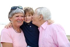 Happy kid getting kissed by grandpa and hugged by grandmother Stock Images