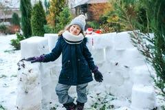 happy kid girl building snow castle on winter holidays Stock Photos
