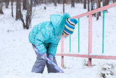 Happy kid girl child outdoors in winter digging snow with toy sp Stock Photography