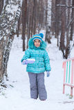 Happy kid girl child outdoors in winter digging snow Stock Photos