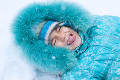 Happy kid girl child outdoors in winter lying on snow catching s Stock Photos