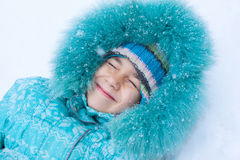 Happy kid girl child outdoors in winter lying on snow Stock Photography