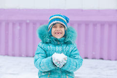 Happy kid girl child outdoors in winter playing holding snow Royalty Free Stock Image