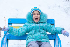 Happy kid girl child outdoors in winter sitting on bench Stock Photos