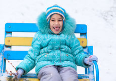 Happy kid girl child outdoors in winter sitting on bench Royalty Free Stock Photos