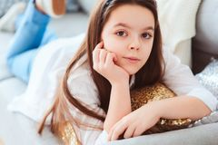 Happy kid girl close up portrait. Preteen relaxing at home on cozy couch Royalty Free Stock Image