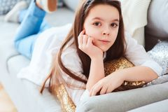 Happy kid girl close up portrait. Preteen relaxing at home on cozy couch Stock Image