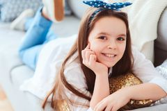 Happy kid girl close up portrait. Preteen relaxing at home on cozy couch Royalty Free Stock Photo