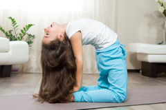 Happy kid girl doing yoga at home Stock Photos