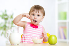 Happy kid girl eating food itself with spoon Stock Images