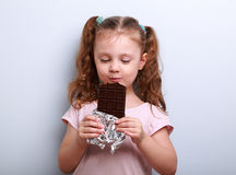 Happy kid girl eating health dark chocolate with pleasure and cl Stock Image