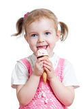 Happy kid girl eating ice cream in studio isolated Royalty Free Stock Images