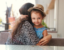 Happy kid girl embracing her beautiful mother outdoor summer bac Stock Images