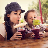 Happy kid girl and funny emotional mother drinking berries smoot royalty free stock photos