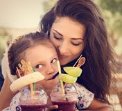 Happy kid girl and funny emotional mother drinking berries smoothie juice together in street summer outdoor cafe. Closeup. Toned portrait stock photos