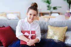Happy kid girl with gift for birthday or christmas posing at home in modern scandinavian interior Stock Image