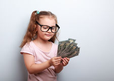 Happy kid girl in glasses looking and counting the money. On blue background Royalty Free Stock Photography