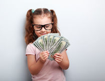 Happy kid girl in glasses looking on money and counting the prof Royalty Free Stock Photography