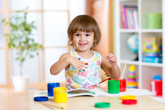 Happy kid girl with hands painted color paints Royalty Free Stock Images
