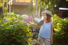 Happy kid girl in hat playing little gardener and helps to water flowers. Happy child playing little gardener and watering hydrangea bush in sunny summer garden Stock Photo