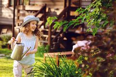 Happy kid girl in hat playing little gardener and helps to water flowers Royalty Free Stock Photos