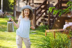 Happy kid girl in hat playing little gardener and helps to water flowers. On summer vacation Royalty Free Stock Images