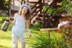 Happy kid girl in hat playing little gardener and helps to water flowers. On summer vacation Royalty Free Stock Photography
