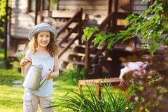 Happy kid girl in hat playing little gardener and helps to water flowers. On summer vacation Royalty Free Stock Photos