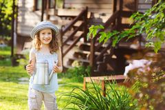 Happy kid girl in hat playing little gardener and helps to water flowers Stock Photos