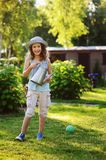 Happy kid girl in hat playing little gardener and helps to water flowers. Vertical portrait of happy child girl in gardener hat playing with watering can in Royalty Free Stock Photo