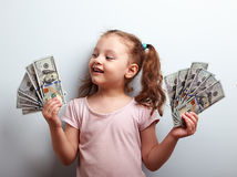 Happy kid girl holding cash dollars and looking with smile. On blue background Royalty Free Stock Photography
