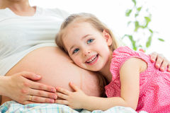 Happy kid girl hugging pregnant mother Stock Photo