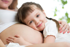 Happy kid girl hugging pregnant mother's belly Royalty Free Stock Images