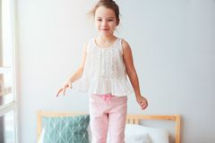 happy kid girl jumping on bed in early morning Stock Images