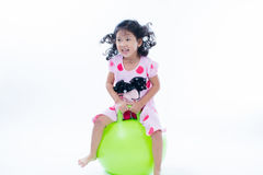 Happy kid girl jumping on bouncing ball Royalty Free Stock Image