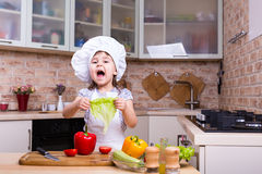 Happy kid girl on kitchen with fresh vegetables Stock Images