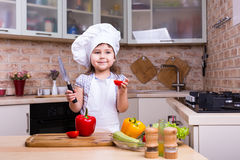 Happy kid girl on kitchen with tomato and knife royalty free stock photo