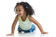 Happy kid girl lying on floor and playing isolated. On white stock photography