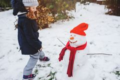 Happy kid girl making snow man on Christmas vacations on backyard. Winter outdoor activities for kids Royalty Free Stock Photos