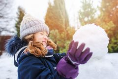 Happy kid girl making snow man on Christmas vacations on backyard. Winter outdoor activities for kids stock photo