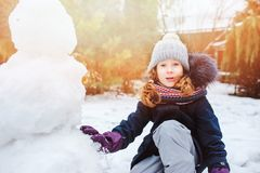 Happy kid girl making snow man on Christmas vacations on backyard. Winter outdoor activities for kids royalty free stock photography