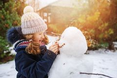 Happy kid girl making snow man on Christmas vacations on backyard. Winter outdoor activities for kids royalty free stock image