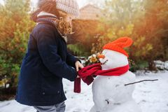 Happy kid girl making snow man on Christmas vacations on backyard. Winter outdoor activities for kids Stock Photos