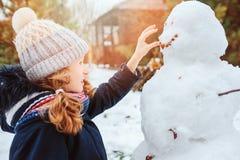 Happy kid girl making snow man on Christmas vacations on backyard Stock Photos