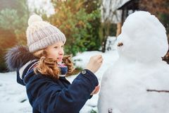 Happy kid girl making snow man on Christmas vacations on backyard Royalty Free Stock Image