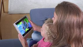 Happy kid girl with mommy watch family movie video on tablet computer screen