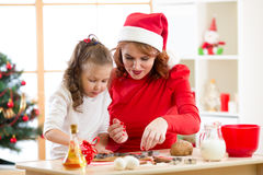 Happy kid girl and mother baking x-mas cookies together at festive decorated room Stock Photography