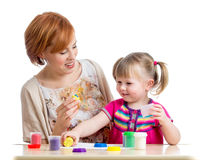 Happy kid girl and mother play with colorful clay toy Stock Images