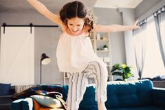 Happy kid girl playing at home in weekend morning and jumping on couch royalty free stock image
